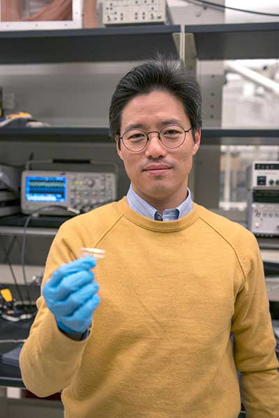 Junseok Chae in his lab holding an implant