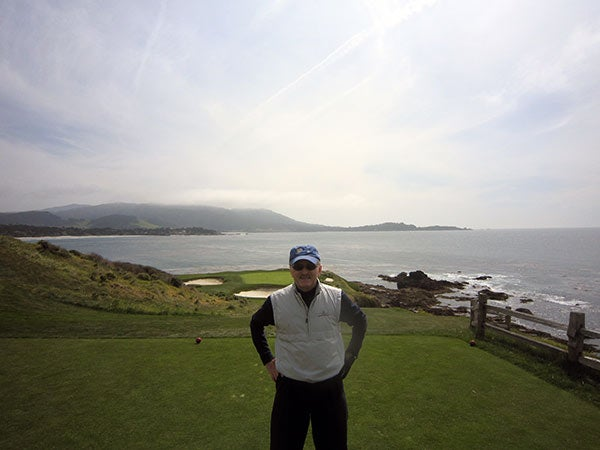 Constantine Balanis stands on the golf course that is overlooking a body of water.