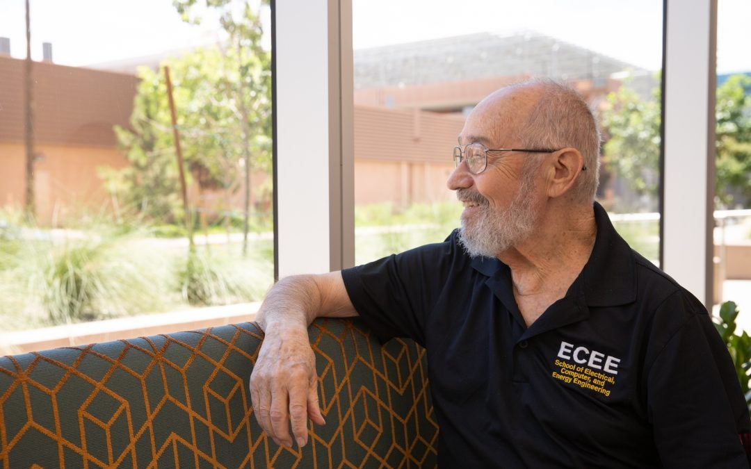 Joseph Palais sits on a couch on the first floor of the Mirabella at ASU looking out floor to ceiling windows onto the ASU Tempe campus