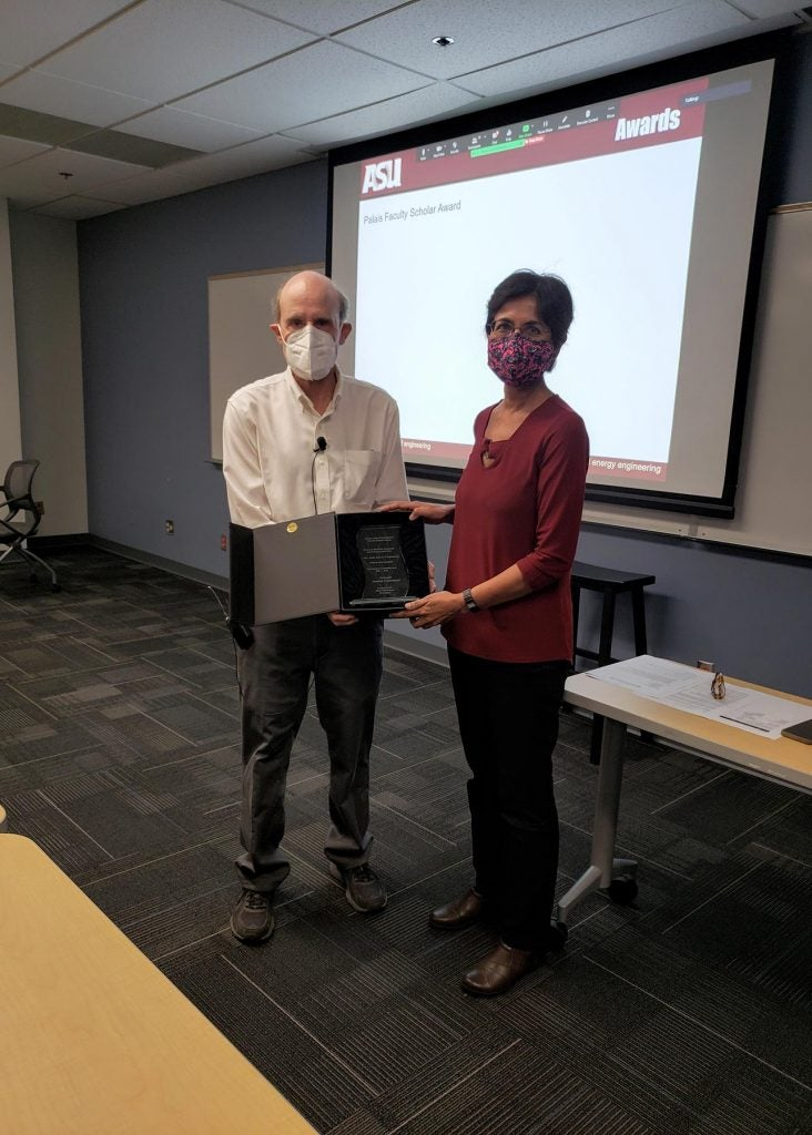 Stephen Phillips and Chaitali Chakrabata pose in a classroom holding the Joseph Palais Distinguished Faculty Award